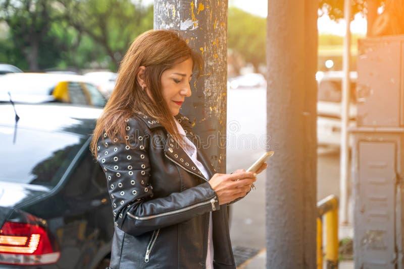 Una mujer madura sonriente que usa su smartphone fotografía de archivo libre de regalías