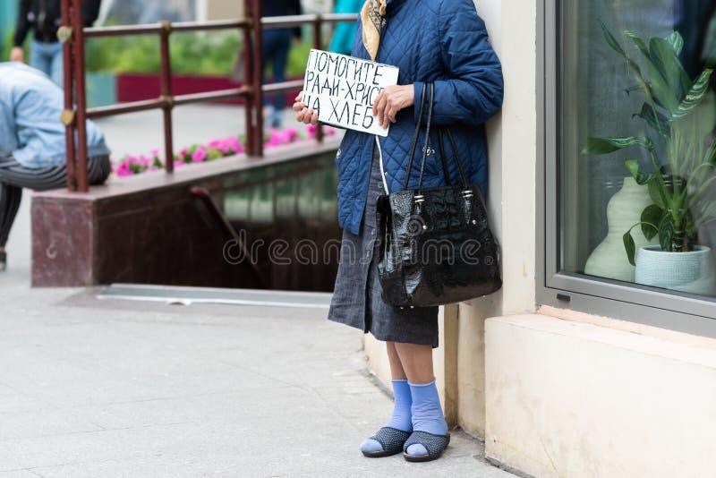 una mujer mayor con cartulina en sus manos pide dinero en la calle Traducción de y x22; Ayuda por el pan de Cristo imagen de archivo