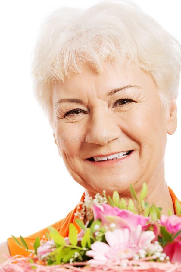 Una mujer mayor con el ramo de flores. fotografía de archivo
