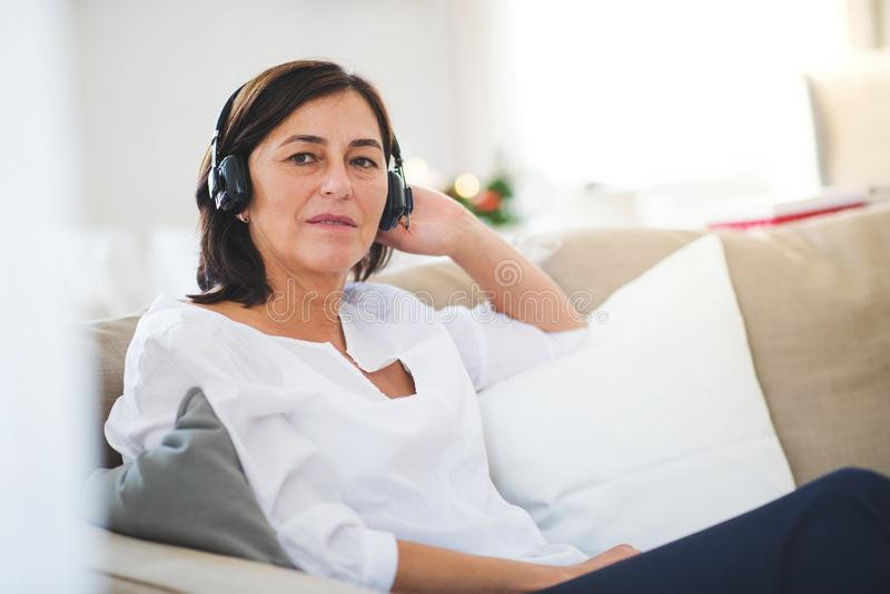 Una mujer mayor con los auriculares que escucha la música en casa en el tiempo de la Navidad imágenes de archivo libres de regalías
