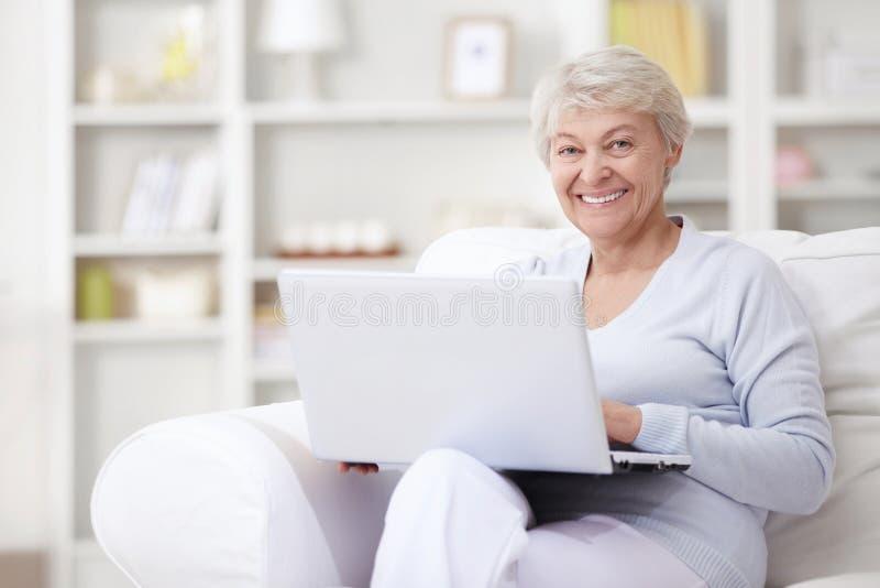 Una mujer mayor con una computadora portátil foto de archivo