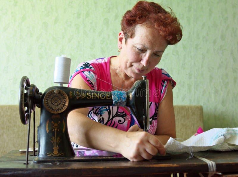 Una mujer mayor cose en un ` del cantante del ` de la máquina de coser de la mano imagen de archivo libre de regalías