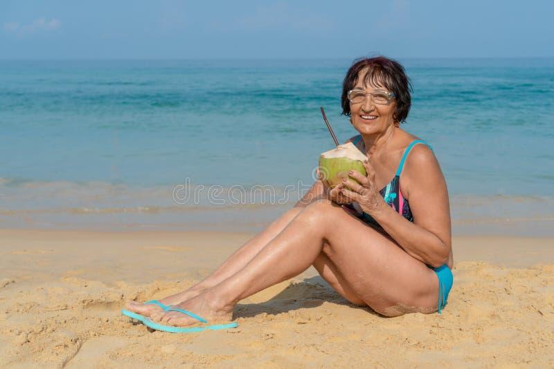 Una mujer mayor en un bañador con un coco que mira la cámara y la risa imagen de archivo libre de regalías