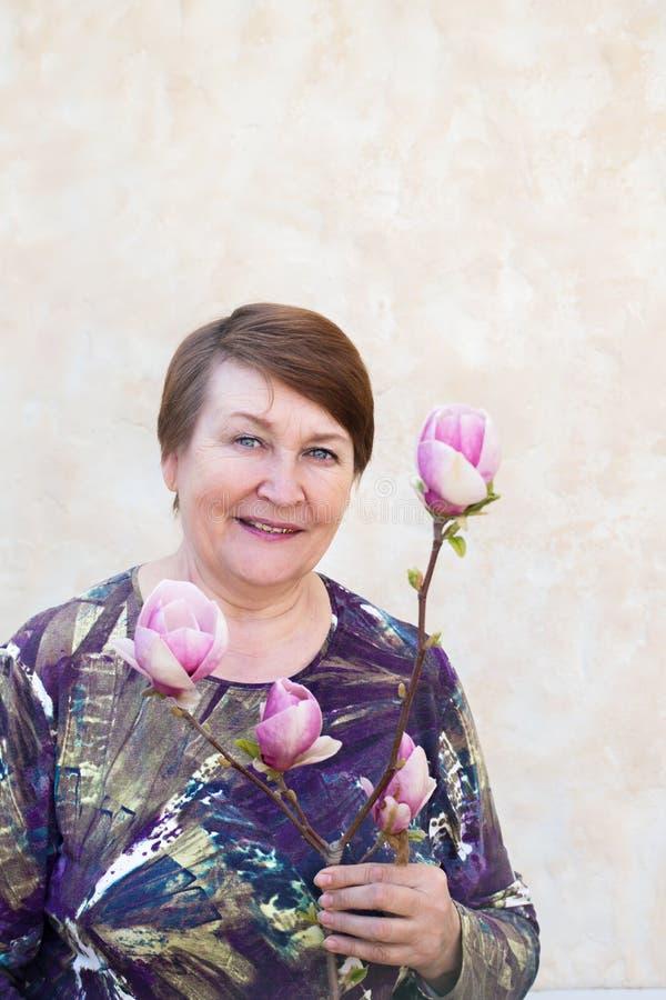 Una mujer mayor lleva a cabo una rama de una magnolia imagen de archivo libre de regalías