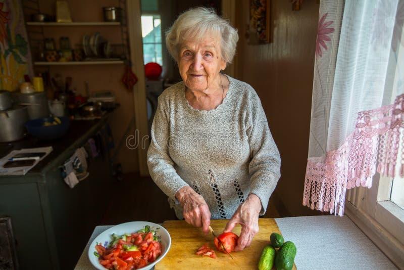 Una mujer mayor prepara una comida fotos de archivo