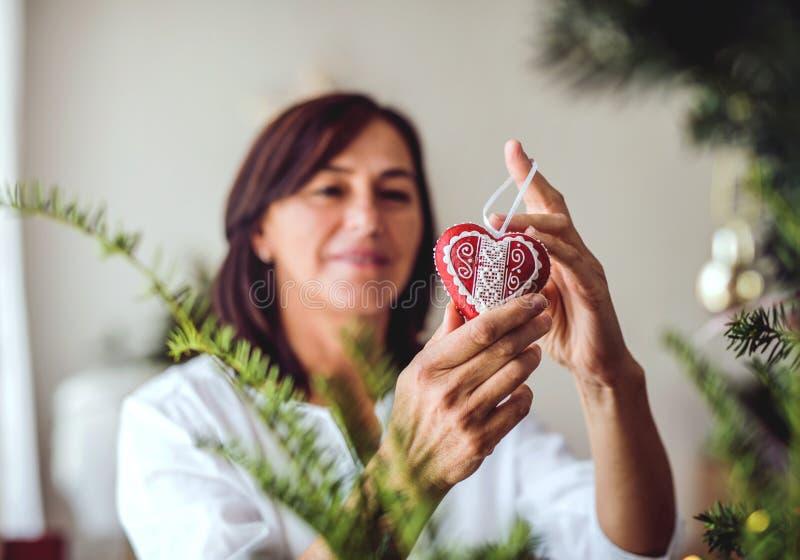 Una mujer mayor que adorna un árbol de navidad en casa foto de archivo libre de regalías