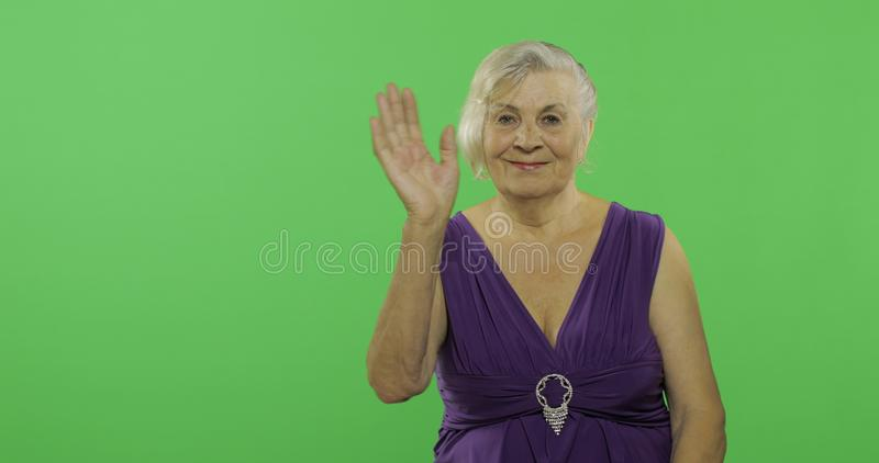 Una mujer mayor que agita a la cámara y a las sonrisas Vieja abuela Llave de la croma fotos de archivo