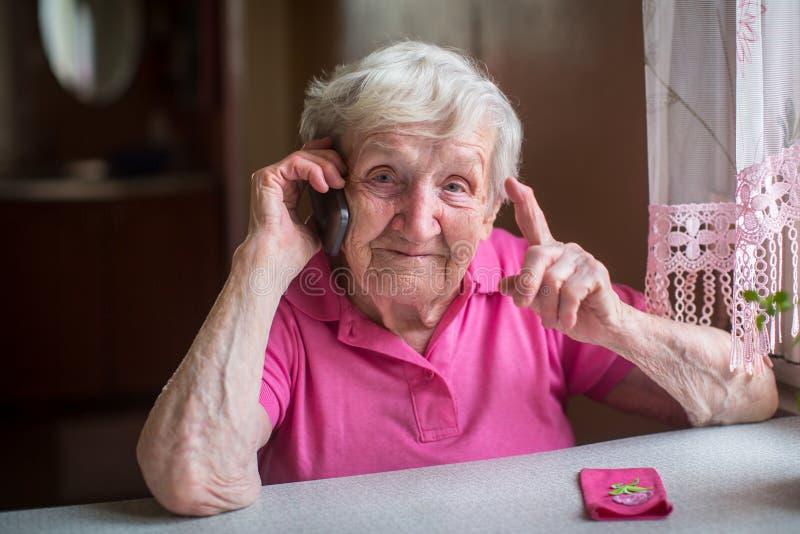 Una mujer mayor que habla en un teléfono móvil imagen de archivo