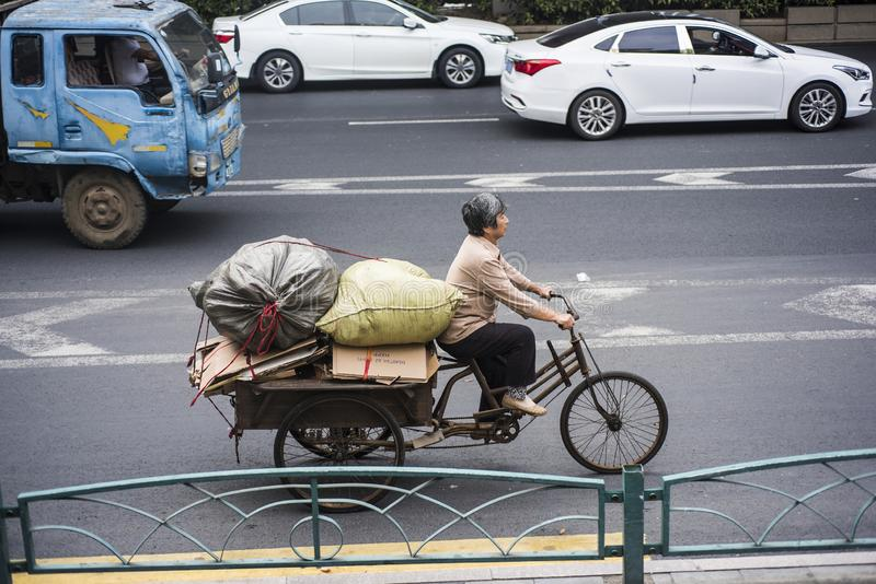Una mujer mayor que monta un triciclo y que tira de las mercancías inútiles adquiridas en el camino fotos de archivo libres de regalías