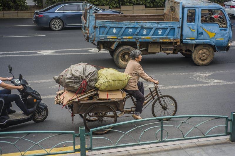 Una mujer mayor que monta un triciclo y que tira de las mercancías inútiles adquiridas en el camino fotografía de archivo