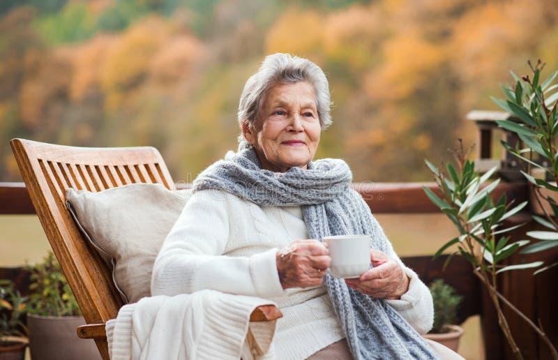 Una mujer mayor que se sienta al aire libre en una terraza adentro en un día soleado en otoño imagenes de archivo