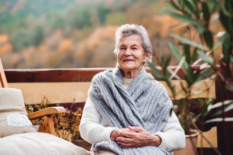 Una mujer mayor que se sienta al aire libre en una terraza en un día soleado en otoño imagenes de archivo