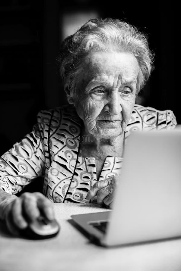 Una mujer mayor que se sienta en una tabla con un ordenador portátil fotos de archivo libres de regalías
