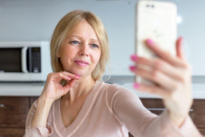 Una mujer mayor que toma un selfie en casa imagenes de archivo