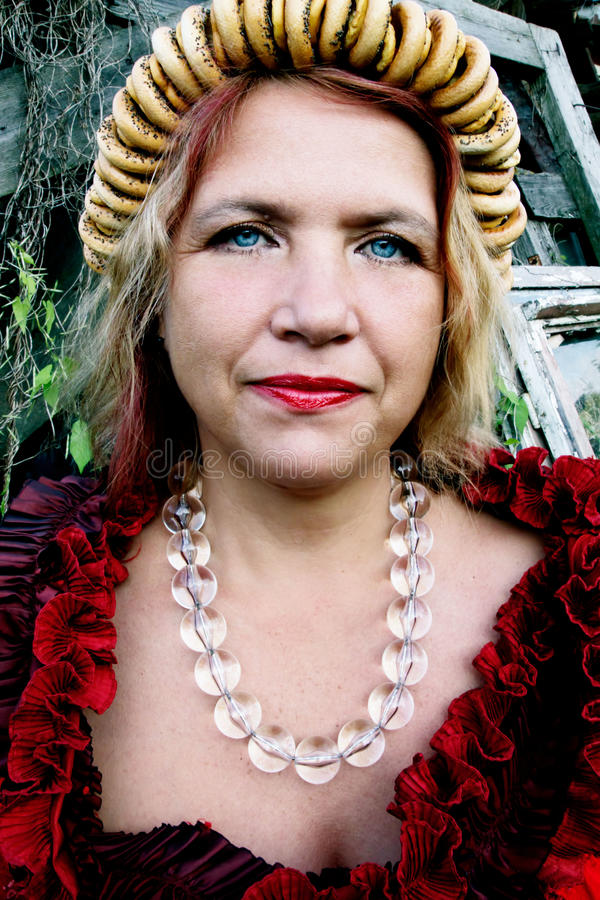 Una mujer mayor se vistió en el viejo estilo ruso con un samovar, un pañuelo brillante en sus hombros y un manojo de panecillos imagenes de archivo
