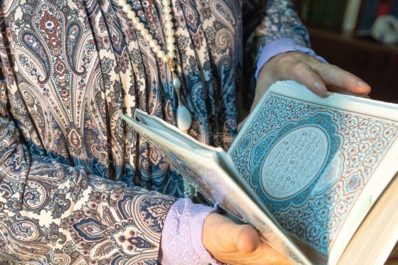 Una mujer mayor sostiene el Corán en sus manos Manos de una persona mayor con un cierre del libro sagrado para arriba Concepto re fotos de archivo libres de regalías