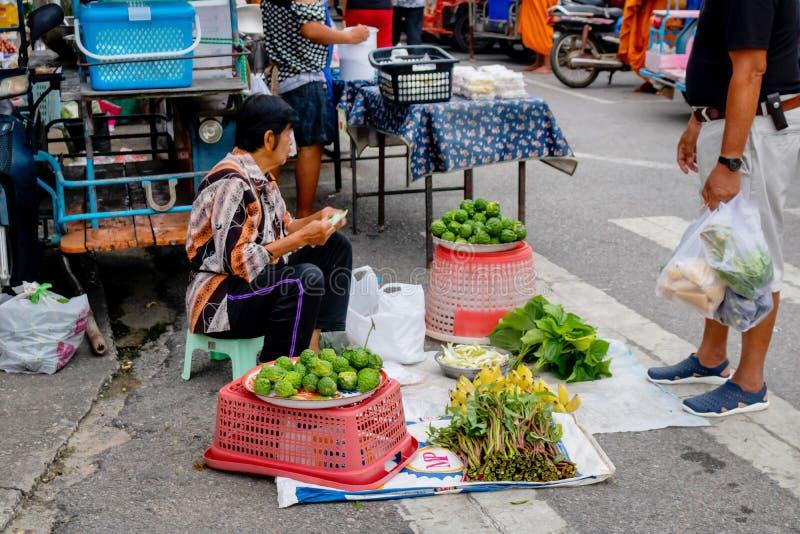 Una mujer mayor tiene que ganar a dinero por venta las verduras ordinarias en el mercado de la mañana de Prachuabkirikhan debido  fotografía de archivo libre de regalías