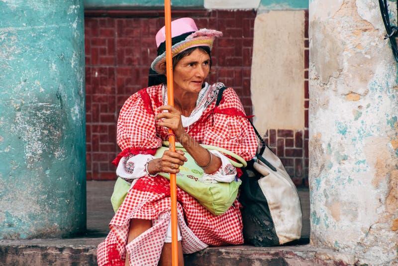 Una mujer mayor vestida maravillosamente se sienta en la ciudad de La Habana, Cuba fotografía de archivo