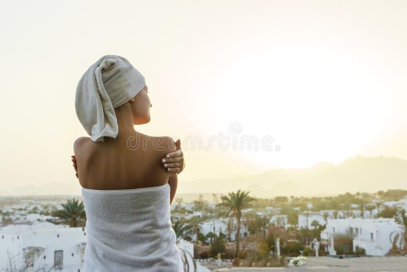 Una Mujer Mira El Sol Poniente Con Una Toalla En Su Cabeza