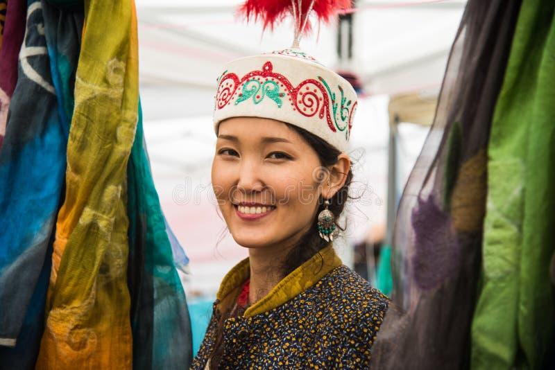Una mujer mongol que vende las sedas y las artesanías de Mongolia Ella trabajaba como voluntario en la 4ta edición de la nación u imagenes de archivo