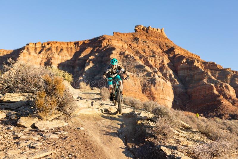 Una mujer monta una bici de montaña sobre un pequeño descenso en el rastro de Jem debajo del mesa de la grosella espinosa en Utah fotos de archivo libres de regalías