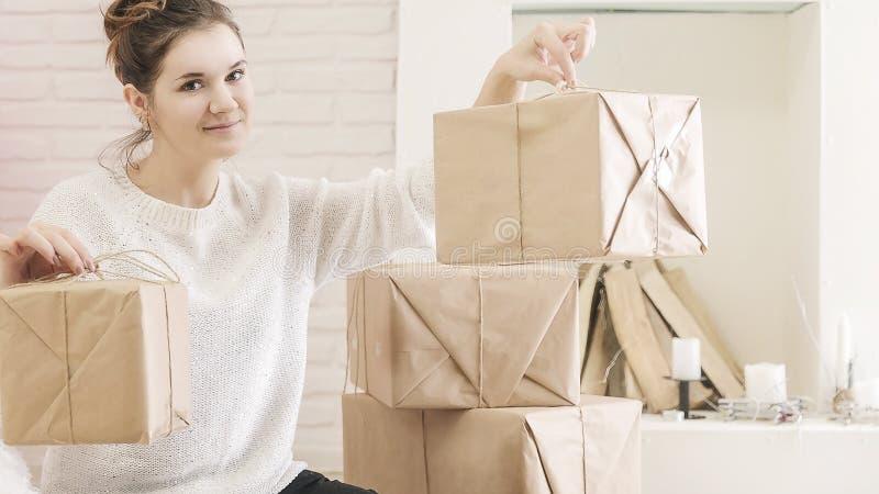 Una mujer morena joven en un suéter blanco se está sentando en el piso en un cuarto brillante y cajas de examen de regalos foto de archivo