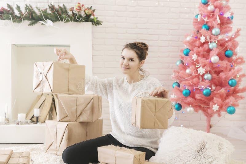 Una mujer morena joven en un suéter blanco se está sentando en el piso en un cuarto brillante y cajas de examen de regalos foto de archivo libre de regalías