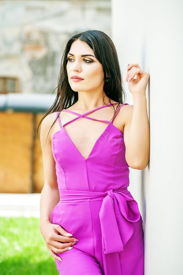 Una mujer morena joven en un traje púrpura el concepto de moda imagen de archivo libre de regalías