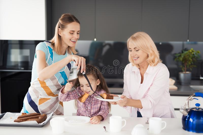 Una mujer, una muchacha y una mujer mayor se están preparando para intentar una empanada hecha en casa que la mujer coció foto de archivo libre de regalías