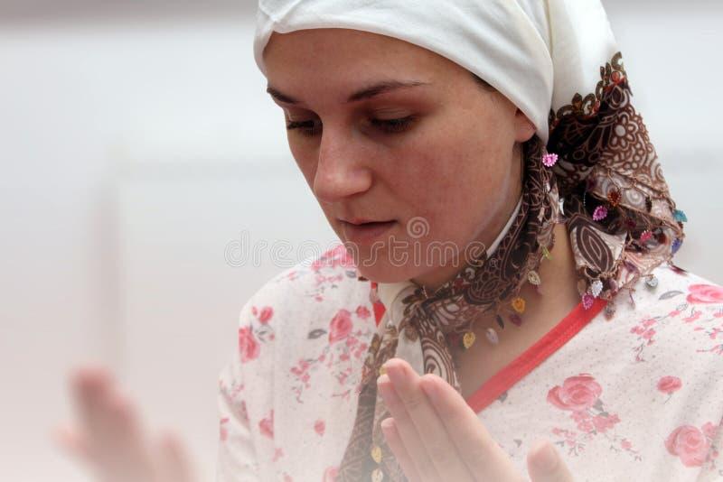Una mujer musulmán joven realiza rezo en la mezquita fotos de archivo