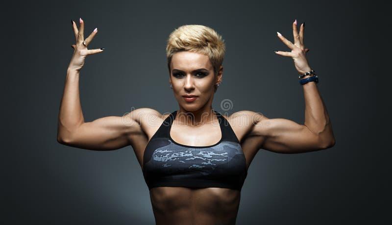 Una mujer muy cabida que plantea su cuerpo muscular fotos de archivo