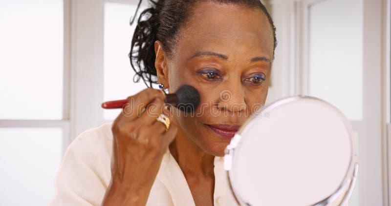 Una mujer negra mayor hace su maquillaje por la mañana en su cuarto de baño foto de archivo