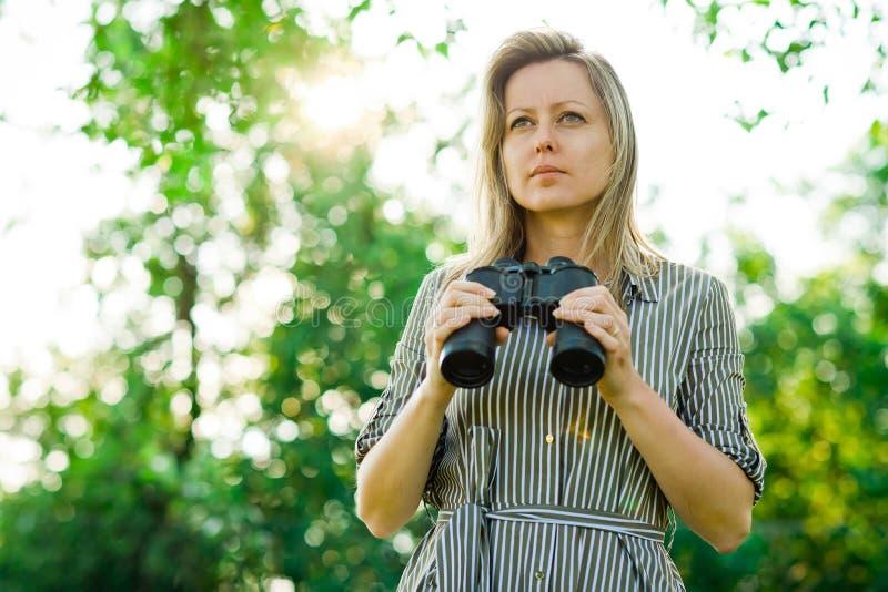 Una mujer observa alrededores el tener de prismáticos - al aire libre fotos de archivo