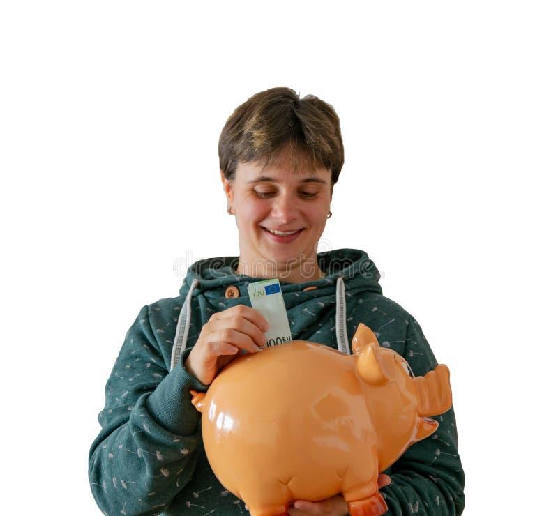 Una mujer pone cientos euros en una hucha fotografía de archivo