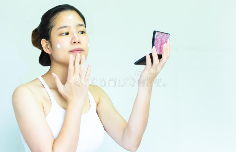 Una mujer puso la crema en su cara foto de archivo libre de regalías