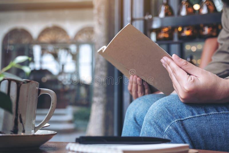 Una mujer que abre un libro con los cuadernos y la taza de café en la tabla de madera fotografía de archivo