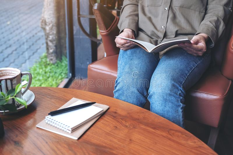 Una mujer que abre un libro con los cuadernos y la taza de café en la tabla de madera fotos de archivo