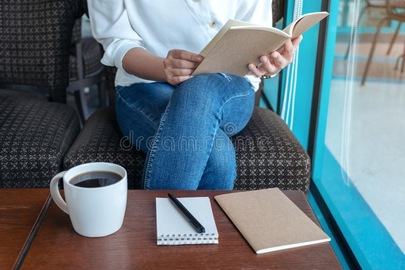 Una mujer que abre un libro para leer con los cuadernos y la taza de café en la tabla de madera en café foto de archivo