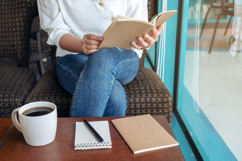 Una mujer que abre un libro para leer con los cuadernos y la taza de café en la tabla de madera en café fotos de archivo libres de regalías