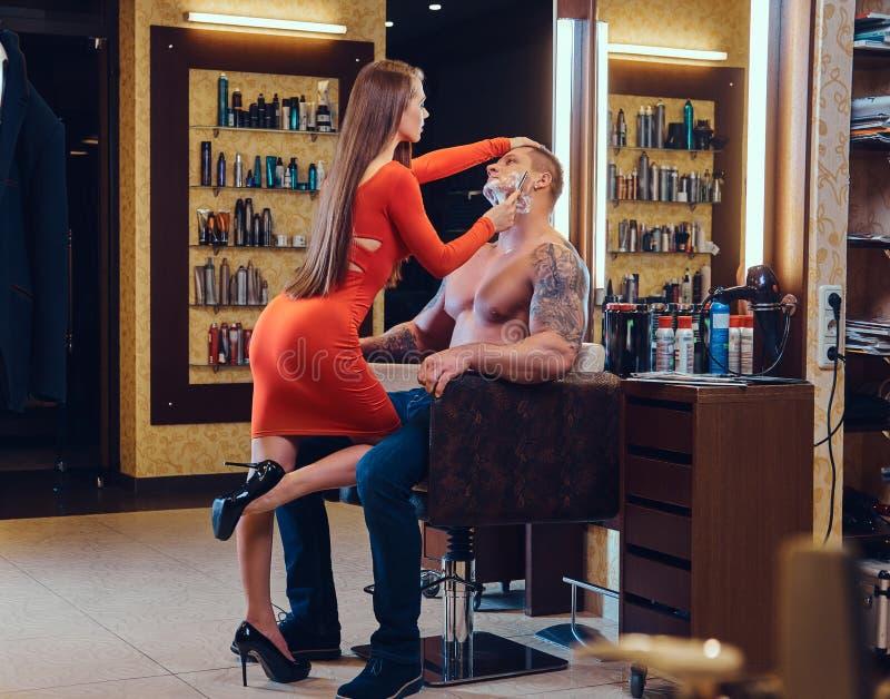 Una mujer que afeita a un hombre fotografía de archivo
