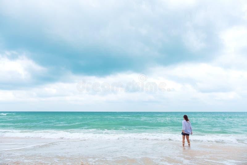 Una mujer que coloca y que mira la opinión sobre la playa con el mar y el cielo azul imágenes de archivo libres de regalías