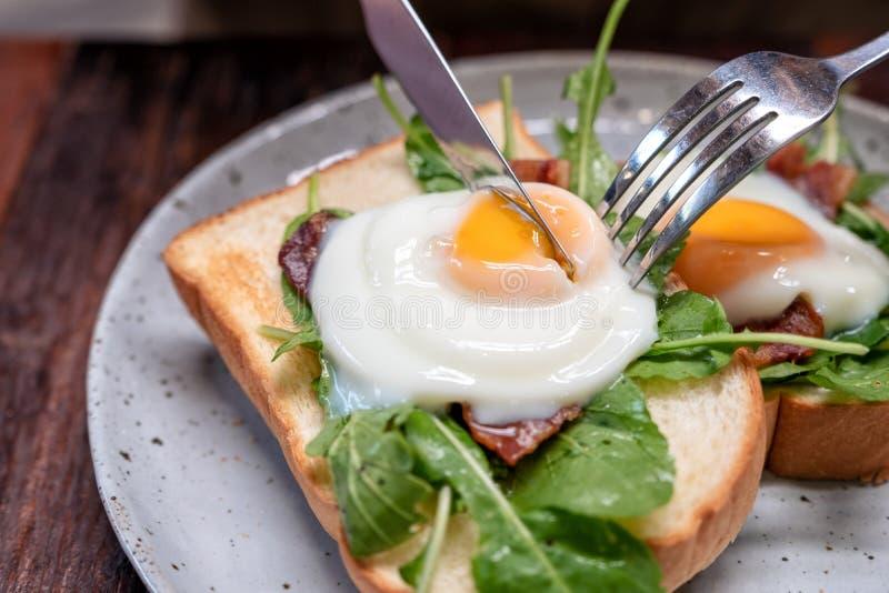 Una mujer que come el bocadillo del desayuno con los huevos, el tocino y la crema agria por el cuchillo y la bifurcación en una p fotografía de archivo