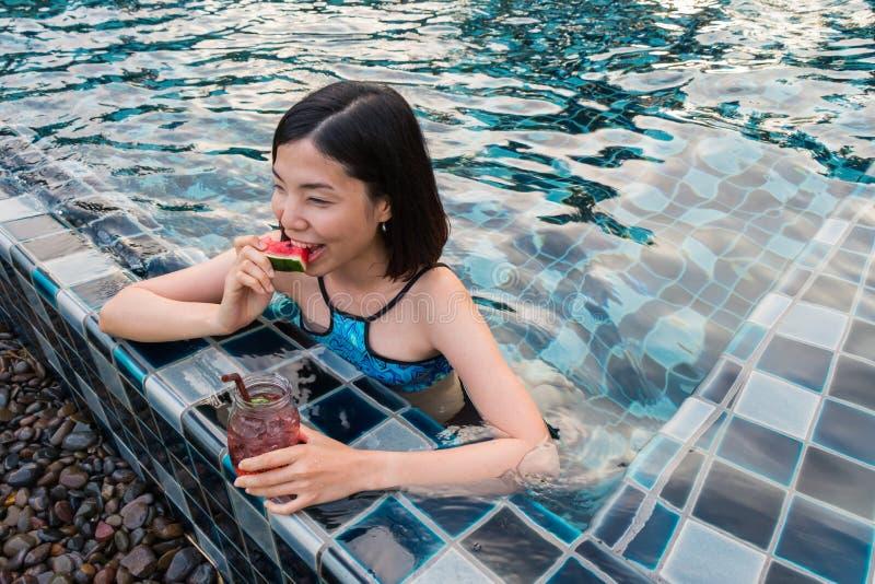 Una mujer que come la sandía en la piscina foto de archivo libre de regalías