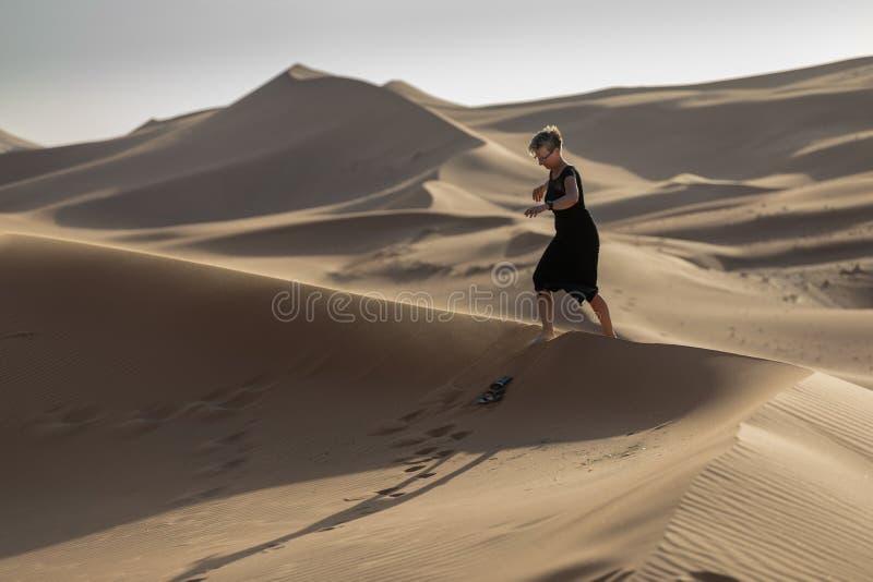 Una mujer que da un paseo en dunas de arena durante puesta del sol fotografía de archivo libre de regalías