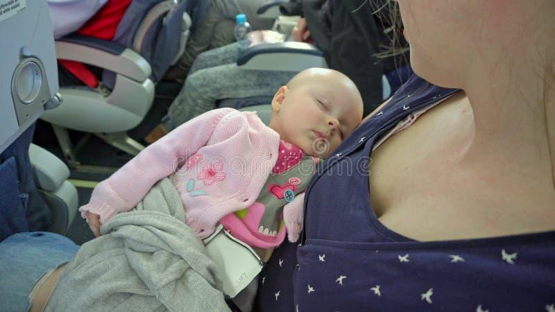 Una mujer que detiene a su niño en un avión imagenes de archivo