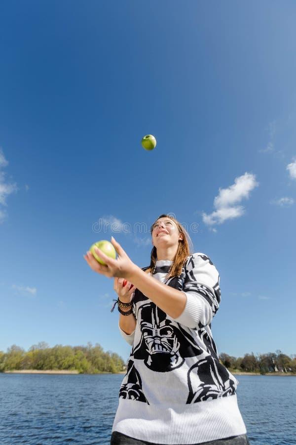 Una mujer que hace juegos malabares con las manzanas fotografía de archivo