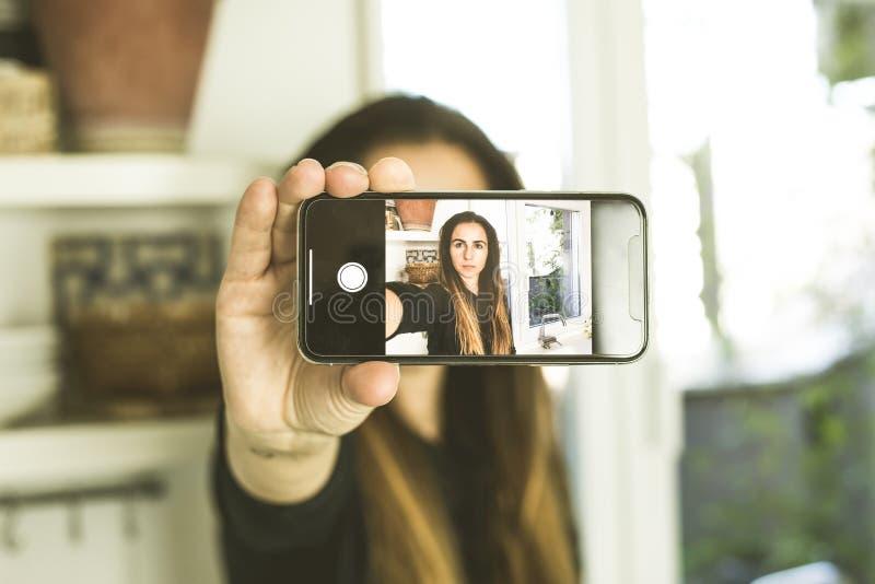 Una mujer que hace un selfi con la expresión seria Mujer que toma una imagen con su teléfono móvil imágenes de archivo libres de regalías