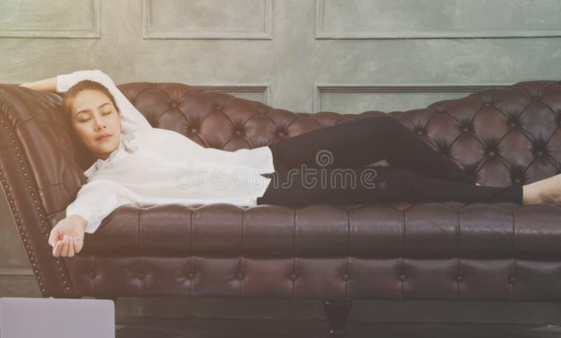 Una mujer que lleva una camisa blanca está durmiendo imagen de archivo