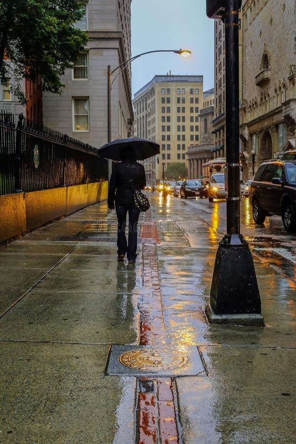 Una mujer que lleva un paraguas y que camina abajo de una calle en la lluvia que sigue el rastro de la libertad de Boston imagen de archivo