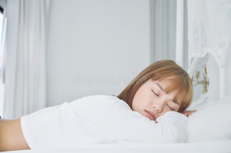 Una mujer que lleva un vestido blanco, ella está durmiendo imágenes de archivo libres de regalías
